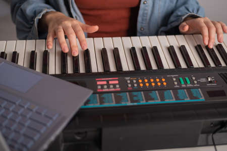 Close-up of female hands on the electric piano. A woman is learning to play the synthesizer on a laptop