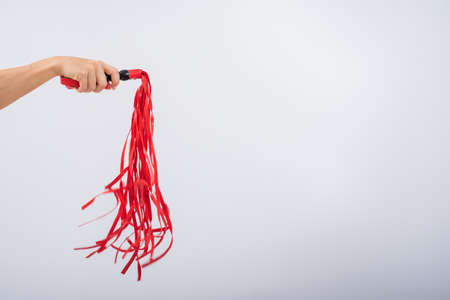 Red leather whip in female hands on a white background. Copy space.