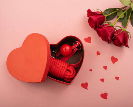 Bdsm set in a box in the form of a heart and red roses on a pink background. Valentines day gift idea