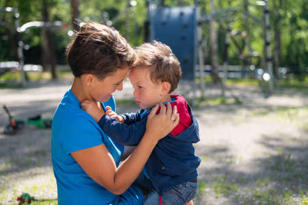 The woman gently hugs her son on the playground. The little boy is naughty and his mother calms him down