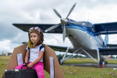 A little girl in a pilots costume with cardboard wings runs on the lawn against the backdrop of the plane. A child in a hat and glasses dreams of flying on an airplane.