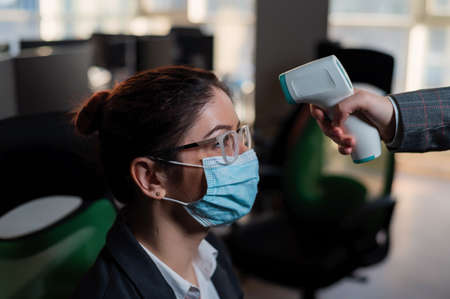 Business woman in medical mask has body temperature measured with electronic thermometer at workplace in office.