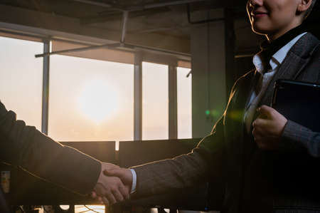 Two young business women shake hands at work. The office staff made a deal 写真素材