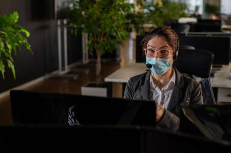 Portrait of a female operator Call Center wearing a medical mask for the desktop 写真素材