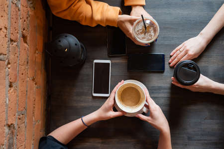 Top view of female hands with smartphones and cups of coffee on a table in a cafe. Three girlfriends drinking coffee.