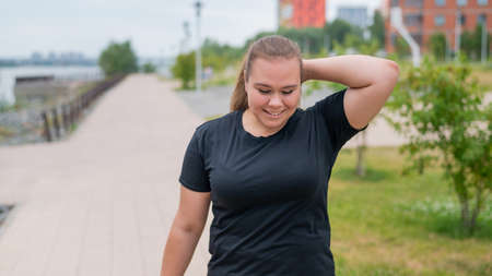 An obese young woman jogging outdoors. Fat beautiful smiling girl in a black tracksuit is engaged in fitness for weight loss on the waterfront. A woman runs on a summer day.