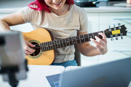 A woman sits in the kitchen during a remote acoustic guitar lesson. A girl learns to play the guitar and watches educational videos on a laptop