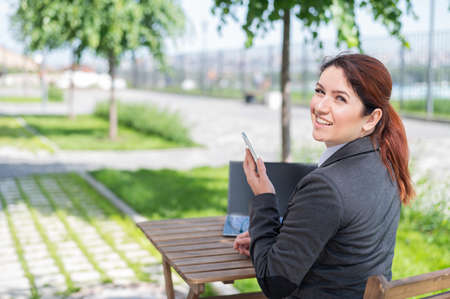 Smilling caucasian woman sits at a wooden table on a summer terrace and uses a smartphone