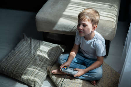 A little boy sits on the floor on a pillow and plays a game console