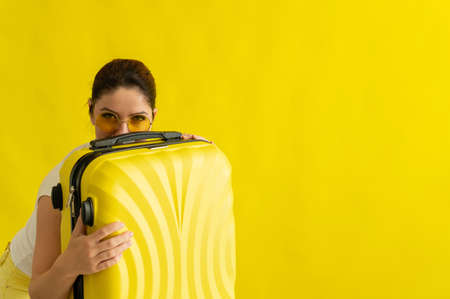A woman in sunglasses hugs a suitcase on a yellow background 写真素材
