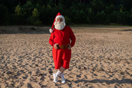Santa claus posing by the sea. Christmas in a hot country