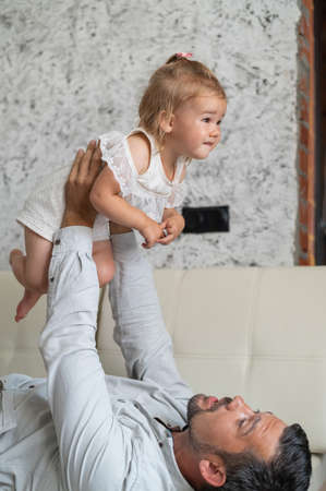 A Caucasian man lies on the couch and holds a little daughter above him. Caring loving dad raised the child up. Happy fatherhood. 写真素材