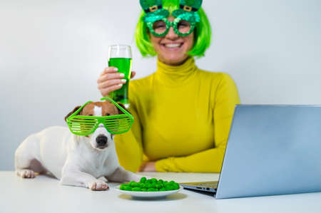 A young woman in a green wig and cheerful glasses drinks beer and bites glazed nuts. A girl sits with a dog at a table and celebrates st patricks day online chatting with friends on a laptop. 写真素材 - 163647080