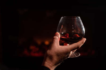 Close-up of a mans hand with a glass of whiskey by the fireplace in the dark. The concept of an elite gentlemens club