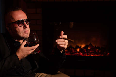A mature man with glasses drinks brandy and smokes a cigar while sitting in an armchair by the fireplace in the dark. The concept of an elite gentlemens club