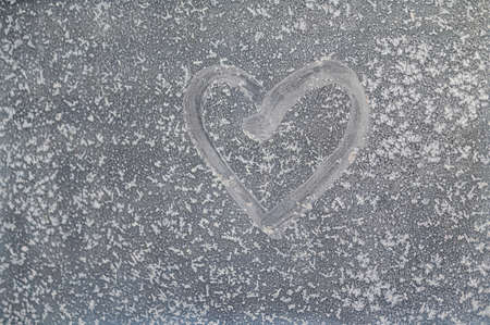 A heart is drawn on a frozen winter window. Valentines day message.