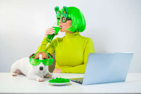 A young woman in a green wig and cheerful glasses drinks beer and bites glazed nuts. A girl sits with a dog at a table and celebrates st patricks day online chatting with friends on a laptop. 写真素材 - 163700122