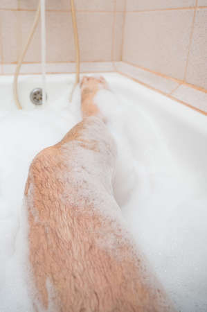 Close-up of male hairy legs in foam. A faceless man is taking a relaxing bath