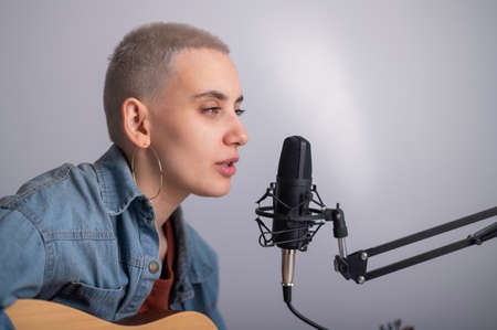 Young hipster woman is recording a song at home recording studio. The girl plays an acoustic guitar and sings into a microphone on a white background