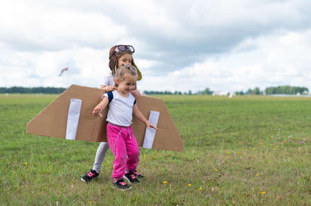 Two little girls in pilots costumes are hugging in the field. Sisters dreams of flying in the sky