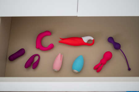 A collection of vibrators and dildos in a white chest of drawers. Private collection of sex toys.