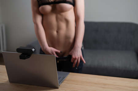 Faceless young woman caresses herself while standing in front of a laptop web camera. The girl masturbates in an online chat Stock Photo