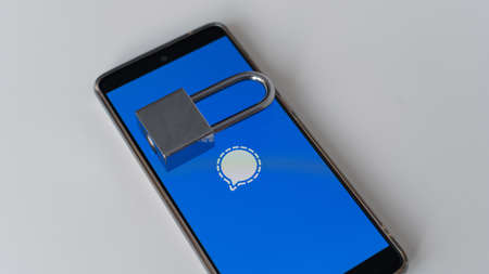 Mobile phone with messenger logo signal and lock on white background. Editorial