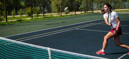 Sportive caucasian woman playing tennis on an outdoor court. Widescreen.