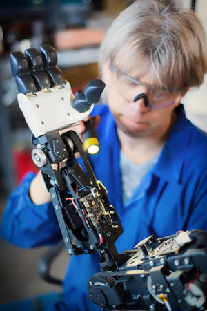 06 april 2019 Russia Novosibirsk: The man assembles a human-like robot and mends his hand