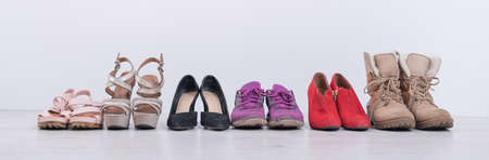 Womens choice of footwear for all seasons. Female shoes in a row on a white background