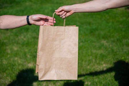 Female courier handing eco cardboard bag to elderly woman outdoors. Delivery of the order to the buyer Stock Photo