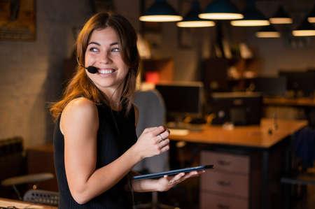 Beautiful caucasian woman in a headset is holding a digital tablet. Portrait of a business woman in the office Foto de archivo