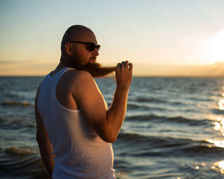 A brutal bald man posing on the beach at sunset in his underwear and touching his red beard. A parody of a glamorous chick