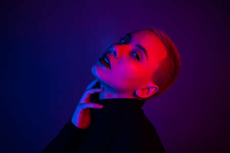 Portrait of a beautiful young woman with short hair in neon light Foto de archivo