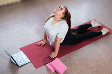 Young Plus Size Woman Stretching At Home Online. Flexible girl practices yoga and watches an online course on a laptop Foto de archivo