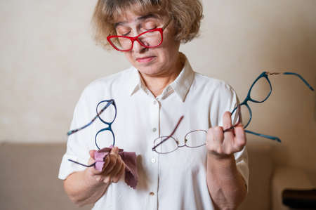 An elderly Caucasian woman chooses glasses from her home collection Foto de archivo