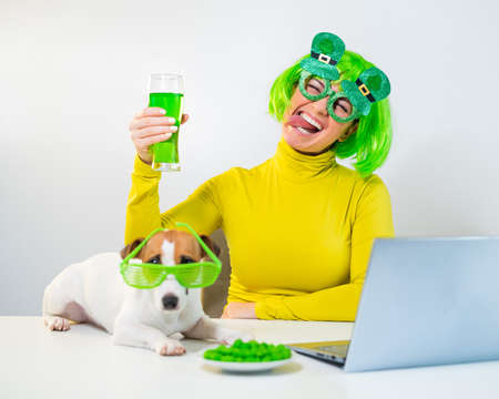 A young woman in a green wig and cheerful glasses drinks beer and bites glazed nuts. A girl sits with a dog at a table and celebrates st patricks day online chatting with friends on a laptop.
