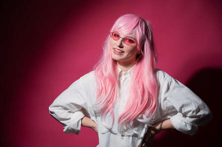 Close-up portrait of a young woman with braces in a pink wig and sunglasses on a pink background.