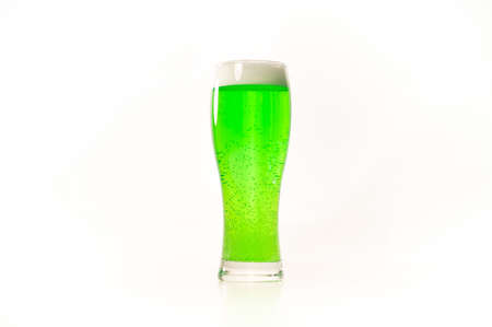 A pint of green beer for st patricks day on a white background. Traditional Irish drink for a holiday. Copy space Foto de archivo