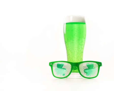 A glass of green beer and funny glasses for st patricks day on a white background. Traditional Irish drink for a holiday. Copy spase.
