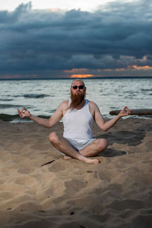 A bald man with a red beard practices yoga on the beach at sunset. A funny dude in a T-shirt and sunglasses meditates on the seashore.