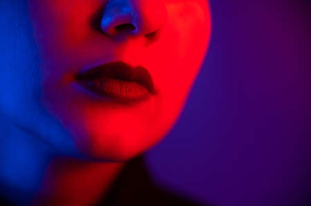 Close-up portrait of beautiful young woman with short hair in neon light. Girl with sensual lips in ultraviolet light.