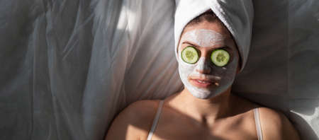 A woman with a towel on her hair and in a clay face mask and cucumbers in front of her eyes lies on the sheet Foto de archivo