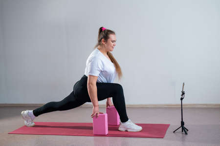 Young fat caucasian woman lunges on a sports mat. Charming plus size girl in sportswear is doing fitness exercises with an online trainer on the phone against a white background