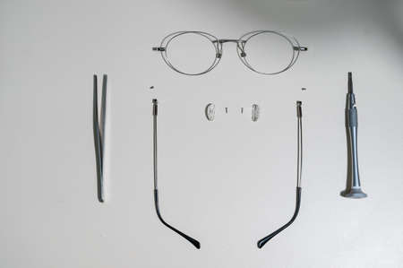 Disassembled glasses frame and tools. Optics work table.
