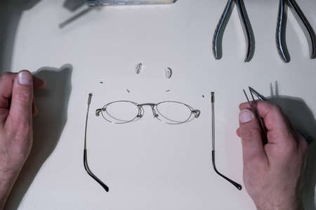 A man repairs a broken eyeglass frame. Close-up of the ophthalmologists hands
