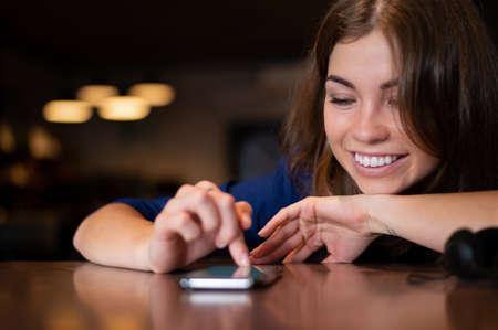 Joyful caucasian woman looks at the phone on the table Foto de archivo