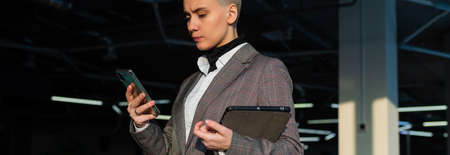 Pensive young woman with short hair uses mobile phone in office.