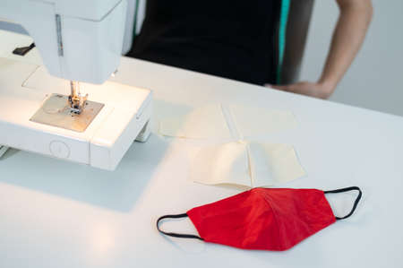 Close-up. A faceless woman sews masks on an electric sewing machine Banque d'images
