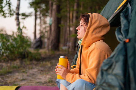 A pensive Caucasian woman in a sweatshirt sits in a tourist tent and drinks from a mug  . Rest at nature. Banque d'images